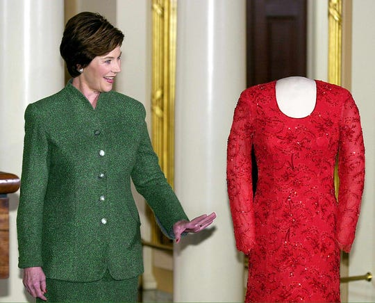 Former first lady Laura Bush poses with the gown she wore to the 2001 Inaugural balls at the Smithsonian's First Ladies Collection, January 20, 2002 at the National Museum of American History in Washington. The red Chantilly lace and satin gown was created by Dallas designer Michael Faircloth.