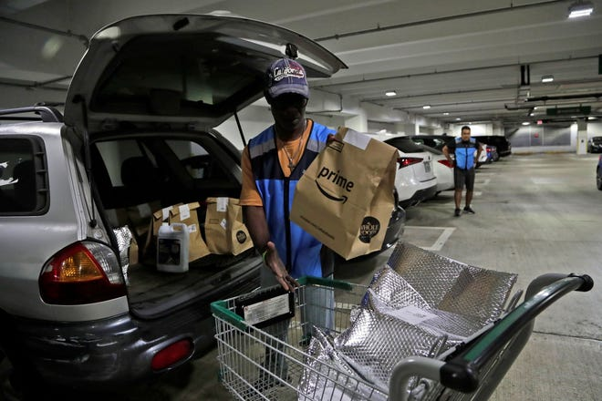 An Amazon Prime food delivery worker loads bags of online grocery purchases into a vehicle in Miami. Congress approved $5 million for technical support to the U.S. Dept. of Agriculture to expand the online purchasing pilot for SNAP recipients. Many say buying groceries online is still too expensive.
