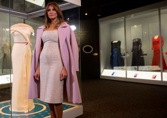 First lady Melania Trump stands alongside the gown she wore to the 2017 inaugural balls as she donates the dress to the Smithsonian's First Ladies Collection at the National Museum of American History in Washington, DC, Oct. 20, 2017.