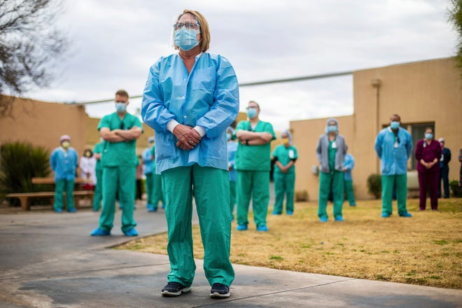 Roxanne Lee, manager of the Tucson, Ariz. Medical Center cath lab, stands with nurses and other colleagues during a ceremony to remember those who have died of the coronavirus, Tuesday, Jan. 19, 2021, in Tucson, Ariz. About 50 hospital staff showed up to the event which coincided with President-elect Joe Biden's national memorial for COVID-19 victims.