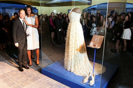 First lady Michelle Obama stands with designer Jason Wu in front of the gown she wore to the 2009 inaugural balls and is now in the Smithsonian's Museum of American History, March 9, 2010 in Washington, D.C.