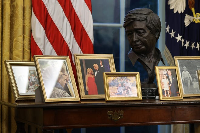 A bronze bust of Mexican-American labor leader César Chávez overlooks photographs on a table behind the Resolute Desk in the Oval Office while President Joe Biden prepares to sign a series of executive orders just hours after his inauguration on Jan. 20, 2021, in Washington, D.C.