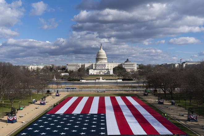 A large American Flag is placed on the National Mall, with the U.S. Capitol behind, ahead of the inauguration of President-elect Joe Biden and Vice President-elect Kamala Harris, Monday, Jan. 18, 2021, in Washington. (AP Photo/Alex Brandon)