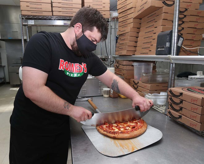 Jeff Miller, an operational specialist at Romeo's Pizza, slices a pepperoni pizza Thursday in Akron. All Romeo's Pizza locations will donate $1 for each pepperoni pizza sold to an Ohio Restaurant Association fund set up to help restaurant workers.