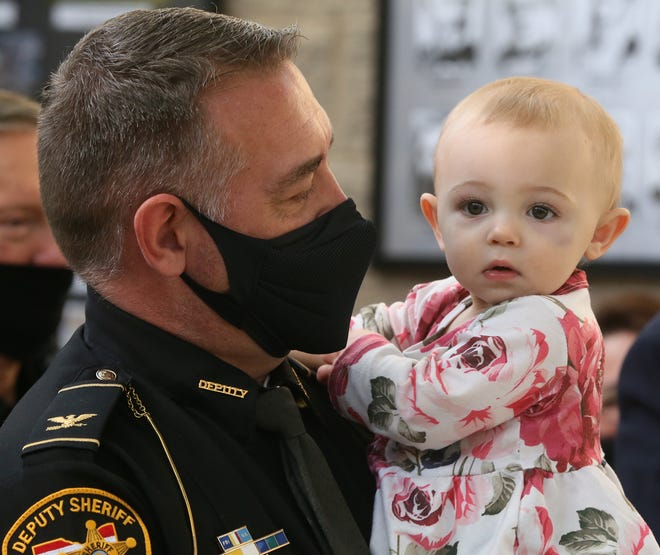 Doug Smith holds his 1-year-old granddaughter, Harper Barner, after being promoted to chief in the Summit County Sheriff's Office during a ceremony Thursday at the sheriff's training center in Green.