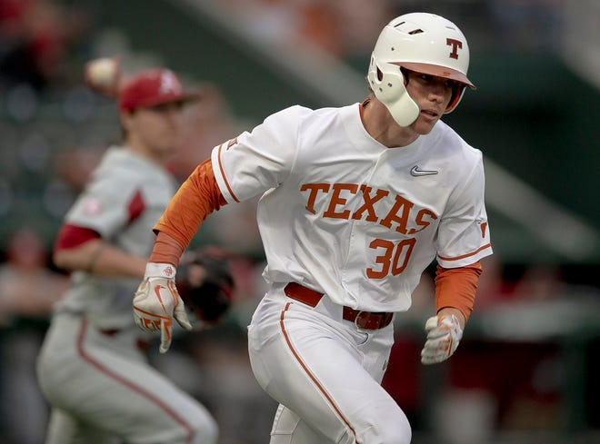 Texas outfielder Eric Kennedy (30) runs to first base as Arkansas pitcher Patrick Wicklander (33) aims to throw him out on March 19, 2019 in Austin.
