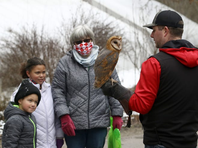 Carter Hill, 5, from left, Peyton Werner, 9, and Sandy Long of Richville watch on Jan. 17 as Will Vaughn, right, of the Raptor Hollow Sanctuary, talks about Bella the barn owl that is part of a partnership with Beech Creek Garden & Nature Preserve.