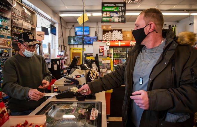 Jessie Hall of Monaca buys lottery tickets Thursday from Mark Dishler of Rochester at Mamula's Mini Market on Ninth Street in Monaca.
