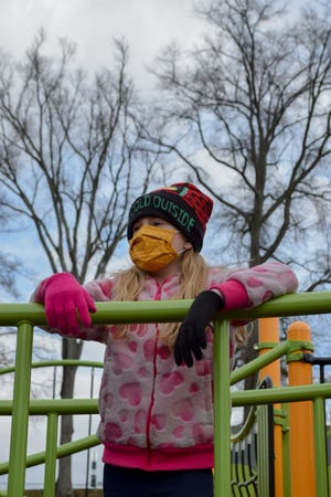 """A young girl wearing a hat saying """"It's Cold Outside"""" hangs out on the playground. She said she likes to wear her mask because it keeps her face warm. Warming centers are available in Belmont County for anyone needing to escape the cold this winter."""