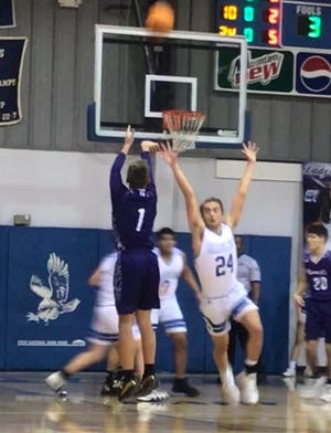 Booneville's Austin Hill (1) launches a three-pointer over Paris' Jesse Wells (24) during the  Jan. 15 game at Paris. Hill led the Bearcats with 15 points in Booneville's 56-45 win.