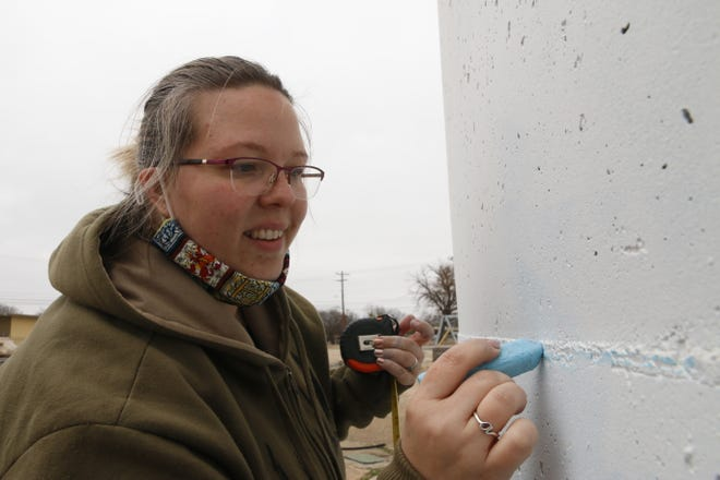 Lehnis Railroad Museum curator Crystal Stanley chalks off a section of the silo on the museum property on a chilly Friday morning earlier this month. Stanley plans to paint an 8-foot-tall mural around the silo's 130-foot circumference.
