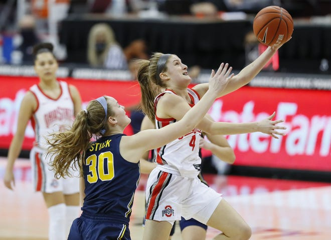 Ohio State guard Jacy Sheldon (4) drives to the basket in the first quarter past Michigan's Elise Stuck. Sheldon's three-point basket in the final minute gave the Buckeyes the lead for good.