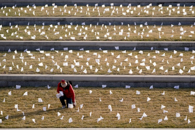 A man places flags Tuesday at the National World War I Museum and Memorial in Kansas City. The 1,665 flags represent the area residents who died in the coronavirus pandemic — part of a national memorial to lives lost to COVID-19.