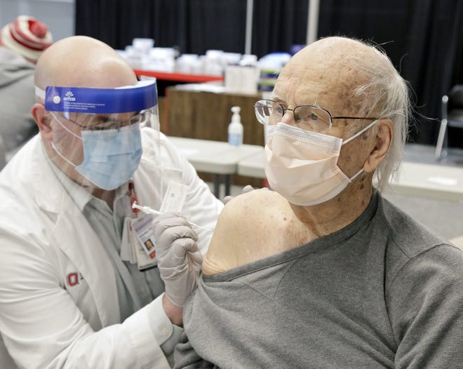 Dr. Kevin Wolowiec gives the COVID-19 vaccine to Arthur Holdford of Dublin on Tuesday, the first day that vaccine was available to the public, at the Schottenstein Center. Ohio State University Wexner Medical Center aimed to vaccinate 1,700 people by the end of the day.