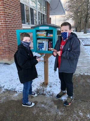 Brothers Hudson and Easton Ross, students at Killbuck Elementary School look over the selection of books in the new LIttle Free Library on the school campus.