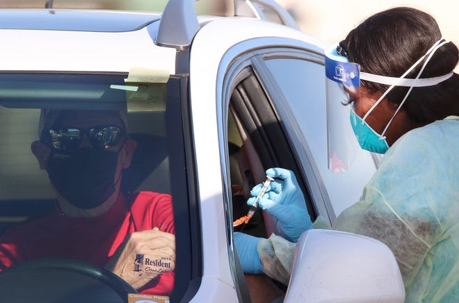 A Florida Department of Health worker inoculates a man with Moderna's COVID-19 vaccine on Thursday, Jan. 21, 2021 at the Volusia County Fairgrounds.