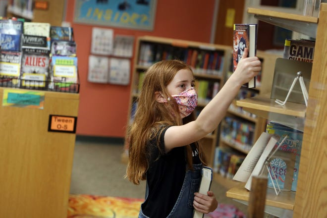 In this file photo, Emma Hutchinson, 11, picks out books during the first day that the Burlington Public Library reopened to the public after closing it doors due to the coronavirus pandemic in Burlington.