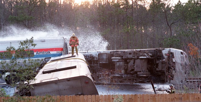 A Jacksonville firefighter stands atop an Amtrak railroad car that overturned after the engine (right) crashed into a truck trying to cross Old Kings Road near Acree Road in 1997.