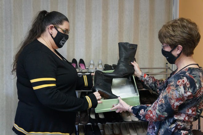 Anna Towns, senior administrative assistant at Trinity Lutheran Church, and Pastor Brenda Roger look over a pair of boots donated to Jana's Closet, a ministry at the church.