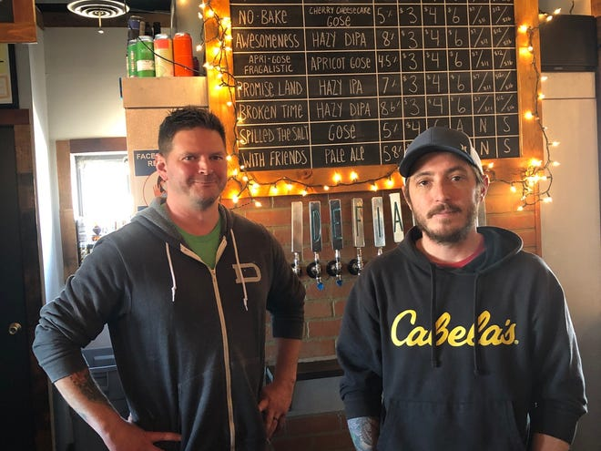 Defiance Brewing Co.'s Matt Bender and Dylan Sultzer, who own the craft brewery with Kenny Gotschalk and a group of investors, stand in front of the beer menu board at their Old Highway 40 location.