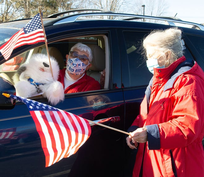 Carolina Village residents Bobbi Seeman, left, and Nancy Polansky chat briefly before the start of Wednesday's car parade through downtown Hendersonville, held to celebrate the inauguration of President Joe Biden.