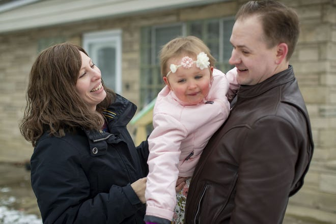 Tara Larson and her husband, Jon, play in the snow with their daughter Tatum, 2, outside their Lamont home Jan. 18, 2021.