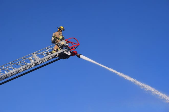 A firefighter sprays water from an extended ladder Thursday at the scene of a building fire on Walnut Street.