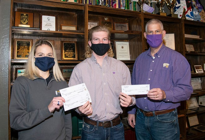 Alpha Gamma Rho President Cameron Kessling, center, presents the proceeds of the recent Smokin' Hog event to Agriculture Instructor Jana Knupp and School of Agriculture Director Andy Baker.