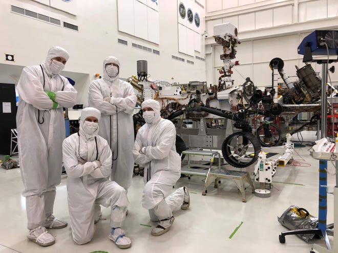 Marcus Whitman alum Tim Canham and his team are pictured with one of the exploration rovers he's worked on. Canham worked on both the software and hardware of these rovers.