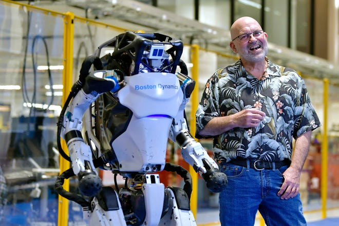 Marc Raibert, founder and chair of Boston Dynamics, stands beside one of the company's Atlas robots during an interview and demonstration, Jan. 13, 2021, at their facilities in Waltham. The company engineered the robot to be able to dance in a fluid manner that is almost human.