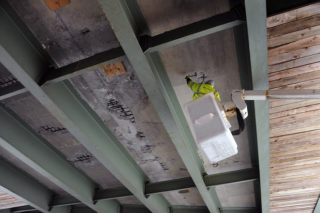 A Mass DOT worker makes a routine inspection under the Mass Pike bridge on Flanders Road in Westborough, Jan. 21. It is one of several area bridges set to be replaced this summer.
