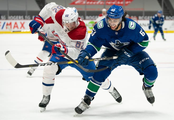 Vancouver Canucks defenseman Jalen Chatfield, right, battles for position with Montreal Canadiens left wing Artturi Lehkonen during the third period Wednesday. Chatfield, the former Utica Comets defenseman, made his NHL debut in Vancouver's home opener.