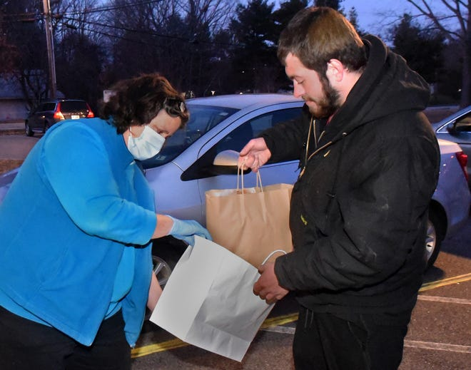 """Operation Blessing's Executive Director Tammy Joslyn finishes putting a meal bag together for Justin McGowan, a homeless individual, at Greenleaf Recreation Center Jan. 20, 2021. It's part of the new """"Take Out Hunger"""" initiative, which is paying area restaurants to cook meals for homeless and other vulnerable individuals. White Heron Coffee and Tea cooked and delivered 40 meals Wednesday night."""