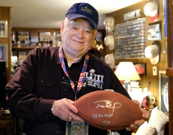 Don Crisman of Kennebunk, Maine, shown here prior to last year's game, holds his prized Tom Brady MVP autographed football from Super Bowl LI, in Houston, Texas. Crisman will be attending his 55th Super Bowl next month in Tampa.