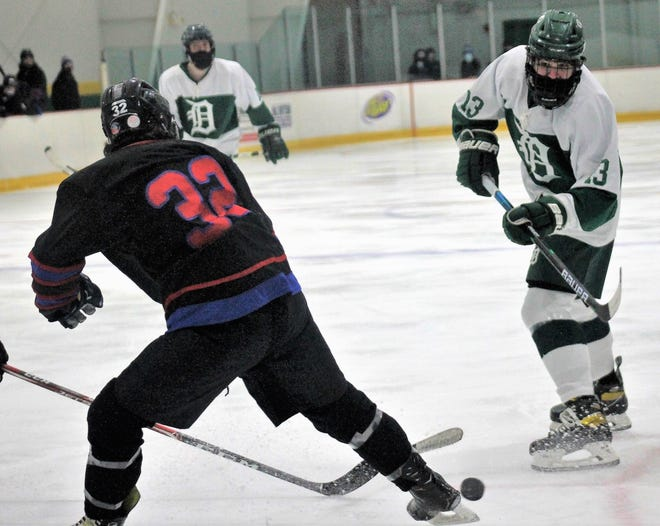 Dover's Brady McDonough, right, tries to make a play with Somersworth/Coe-Brown's James Sawyer defending during Wednesday's Division II boys hockey game at Dover Ice Arena.