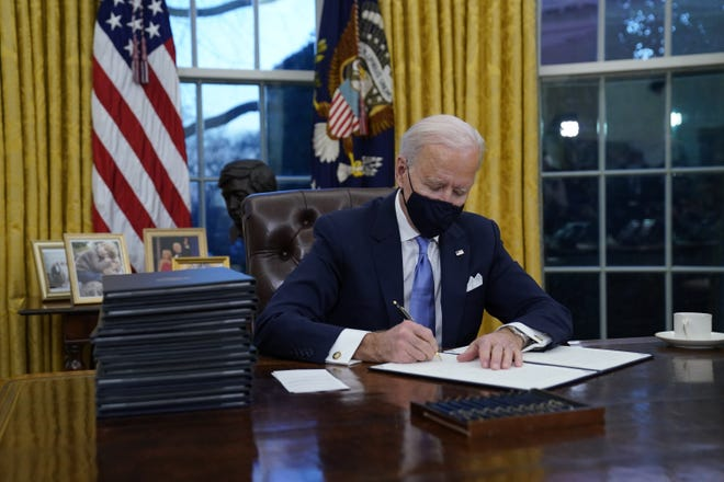 President Joe Biden signs his first executive orders in the Oval Office of the White House on Wednesday, Jan. 20, 2021, in Washington.(AP Photo/Evan Vucci)