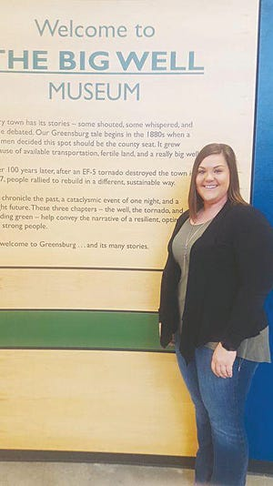 Caitlin Matile, director of the Big Well, stands by a poster kiosk at the Big Well Museum where visitors were down in 2020, but she has high hopes for 2021.