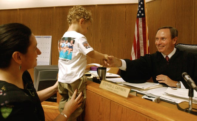 Lisa Rabideau assists her newly adopted son, Justin, as he shakes hands with Judge Stephen J. Capineri at an adoption hearing in 2003.