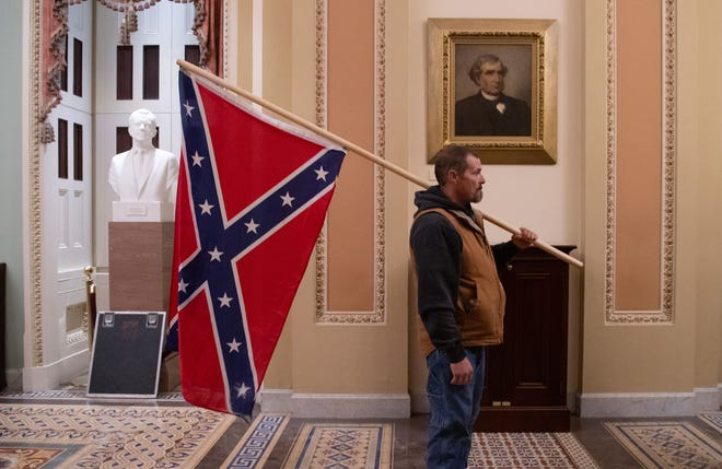 Kevin Seefried, a supporter of President Donald Trump, holds a Confederate flag outside the Senate Chamber during the Jan. 6 riot in the U.S. Capitol. (The portrait behind him is not of Massachusetts Sen. Charles Sumner.)