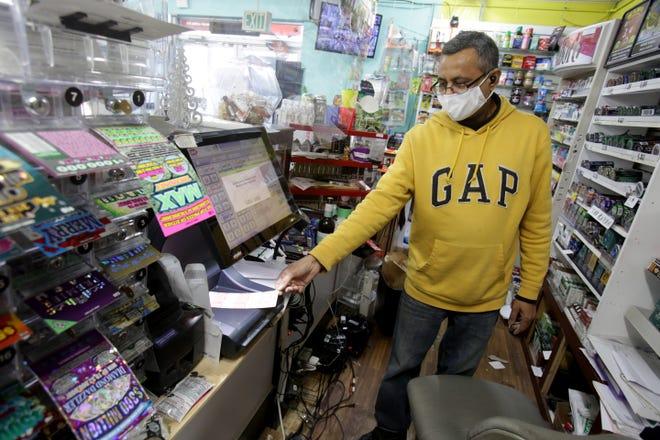 Hanish Patel, owner of Main Avenue Market in Massillon, scans a customer's Mega Millions ticket.