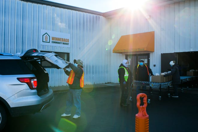 Volunteers like Carl Adrignola of Cherry Valley, left, gather and distribute boxes of food for drive-thru customers at Northern Illinois Food Bank on Thursday, Jan. 21, 2021, in Rockford.