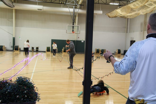 Volunteers untangled, tested and rewound light strings on reels Saturday and Sunday in St. Mary's Fieldhouse. Pictured from left are Katie Trebesch, Barb Pelzel, Aaron Christensen, and Andy Pelzel.