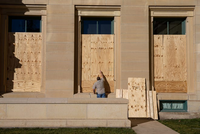 Dwayne Anderson, with the Illinois Secretary of State's physical services carpenter department, uses are marker to number sheets of plywood covering the first floor windows of the Illinois State Capitol prior to them being removed, Thursday, January 21, 2021, in Springfield, Ill. The windows and doors were covered for the days leading up to the inauguration of President Joe Biden out of caution from the possible threat of armed protests after the riots at the U.S. Capitol. The materials were numbered and will be stored in case they need to be used in the future. [Justin L. Fowler/The State Journal-Register]