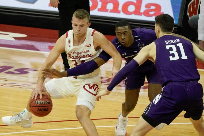 Wisconsin's Brad Davison tries to get past Northwestern's Chase Audige and Robbie Beran (31) during the second half of an NCAA college basketball game Wednesday, Jan. 20, 2021, in Madison, Wis.