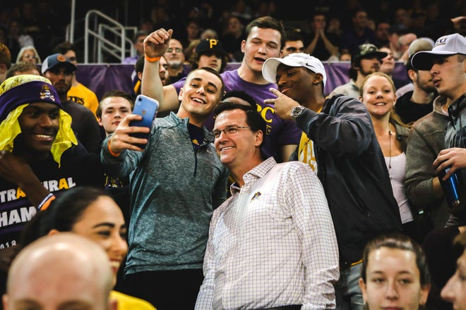 East Carolina athletic director Jon Gilbert poses for a selfie with students in 2019 during a men's basketball game at Minges Coliseum.