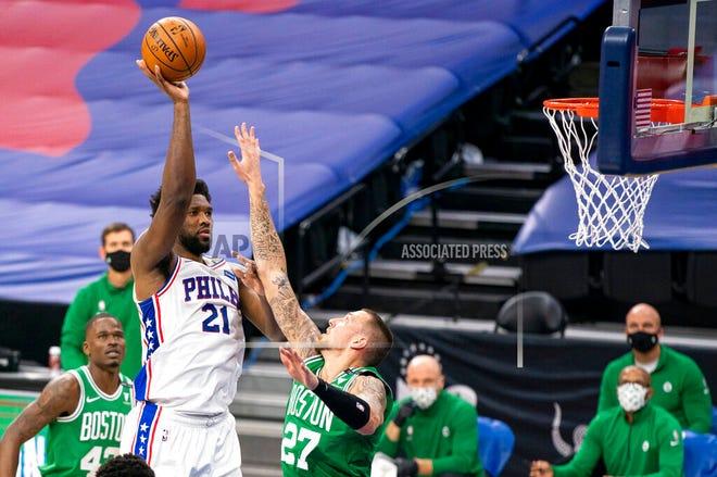 Philadelphia 76ers center Joel Embiid, left, shoots over Boston Celtics center Daniel Theis during the first half of an NBA basketball game Wednesday, Jan. 20, 2021, in Philadelphia.