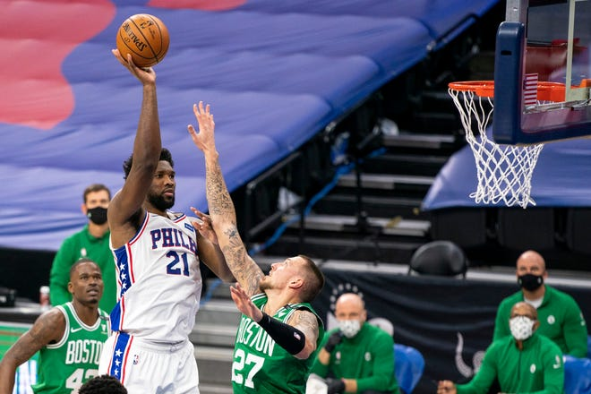 Philadelphia's Joel Embiid, left, shoots over Boston's Daniel Theis during the first half of Wednesday's game.