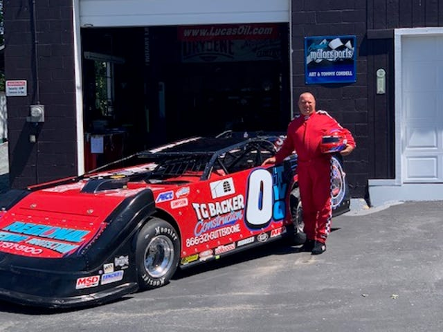 Thomas Cordell poses with his race car, which will carry information about missing children this upcoming season.