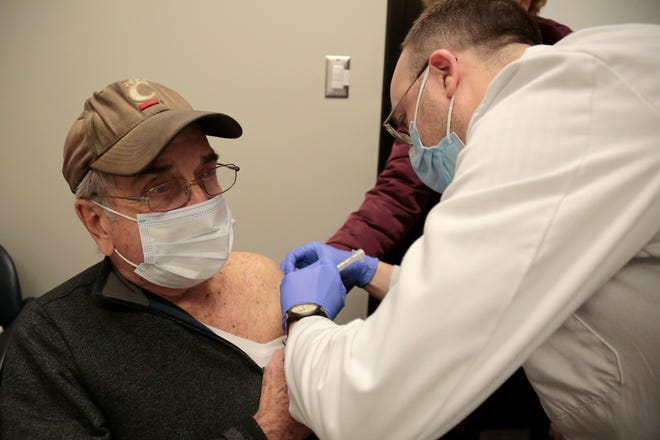 Dick Gerstle, 88, of Anderson Township, receives his first dose of the Moderna COVID-19 vaccine injection from pharmacist Kevin Uchtman at the Kroger pharmacy on Beechmont Road in Anderson Township, Ohio, on Thursday, Jan. 21, 2021.