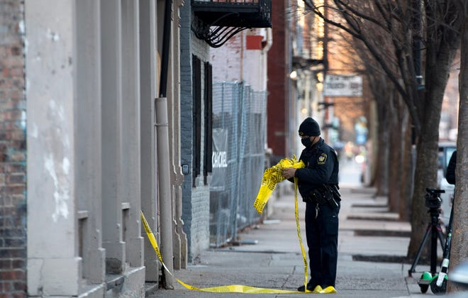 Cincinnati police remove caution tape at the scene of a shooting of a man in the 1500 block of Elm Street in Over-The-Rhine on Thursday, Jan. 21.